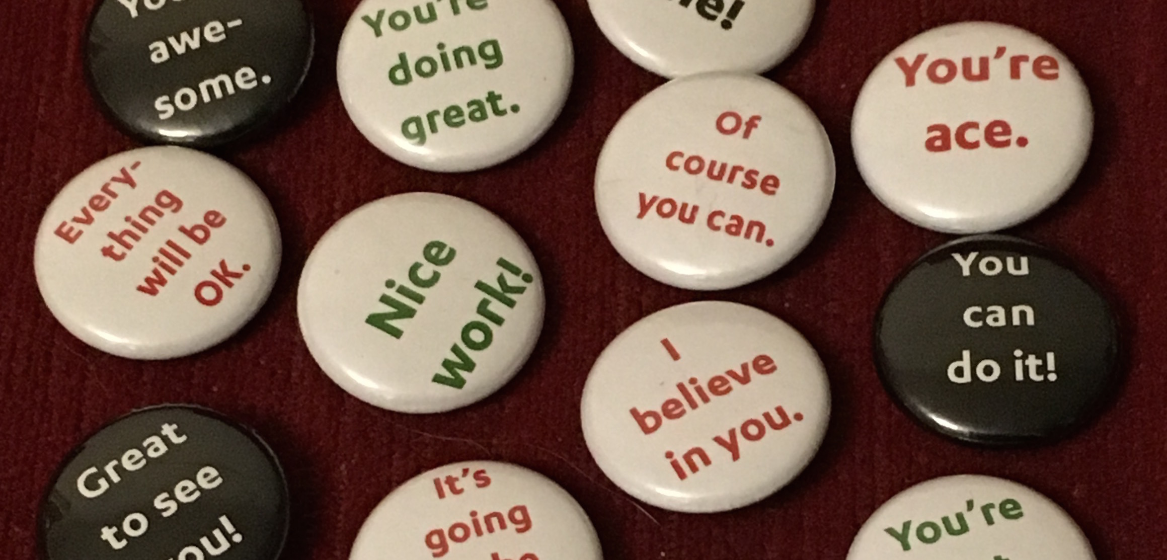 "A number of button badges with phrases on them like ""Of course you can"", ""You're ace"" and ""You can do it!"""